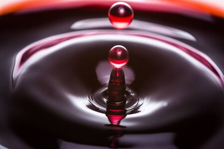 Red wine drop close up image with flash. Stock Photo