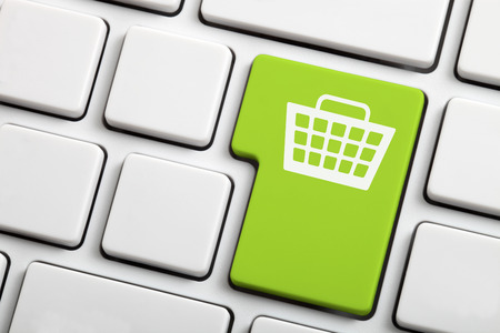 shopping trolley: Close-up of a computer keyboard key with a shopping cart icon.