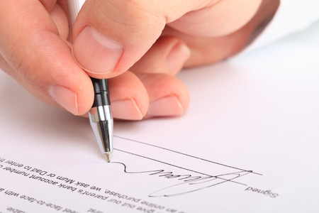 signing a contract: Detail of a male hand signing a contract Stock Photo