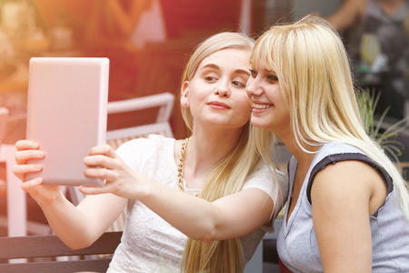 two face: Two young beautiful women making self portrait with tablet
