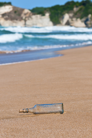 dismay: Message in a bottle washed ashore on a beach