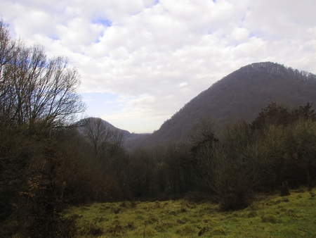 The mountains are sheltered by trees without leaves, waiting for winter