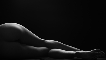 nude body: Sexy woman lies, darkness, light contours, wet skin Stock Photo