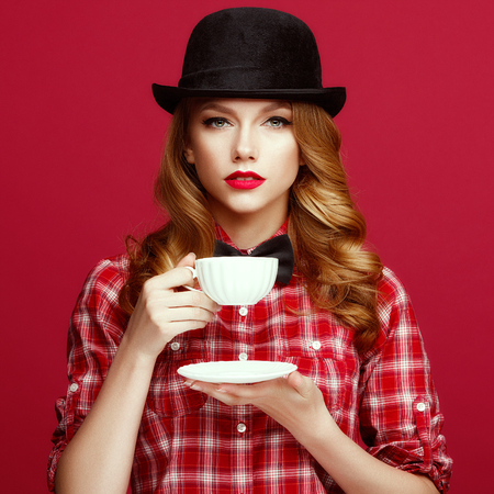 The beautiful blonde in a vintage hat holding a cup of coffee photo