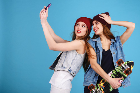 are taking: two young women taking selfie with mobile phone Stock Photo