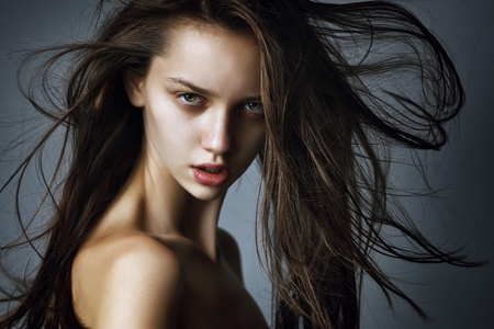 close-up portrait of a beautiful young girl with long hair flying in the wind.