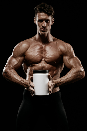 Serious muscular man holding jar with protein