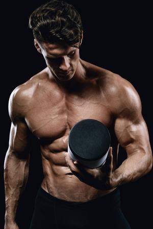 スポーツ栄養の jar ファイルを保持している美しい若い運動男 写真素材 - 74987639