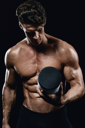 beautiful young athletic man holding a jar of sports nutrition Foto de archivo