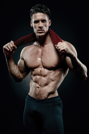 Muscular and fit young bodybuilder fitness male model posing over black background. Foto de archivo