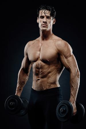 Culturista atletico del tipo di potere bello che fa gli esercizi con la testa di legno. Fitness corpo muscoloso su sfondo scuro. Archivio Fotografico