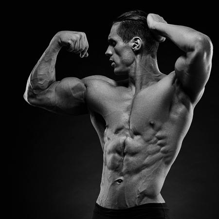 physique: Handsome power athletic young man with great physique. Strong bodybuilder with six pack, perfect abs, shoulders, biceps, triceps and chest.