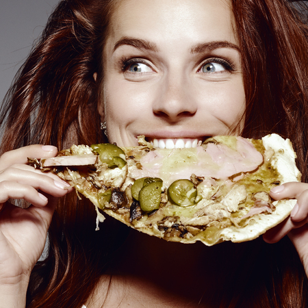 Beautiful close-up portrait of young woman eating pizza. Healthy and junk food concept. Skin care and beauty. Diet. 版權商用圖片