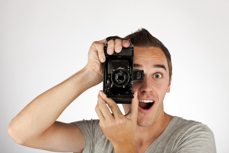 Young happy man with old camera.