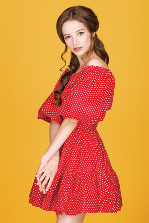 spying: Pin-up of young beautiful girl with curly hair in a red dress on a yellow background.