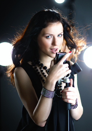 Young woman singing with microphone with back light and flying hair