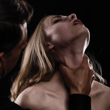 Domestic violence woman being abused and strangled by strong man. on dark background