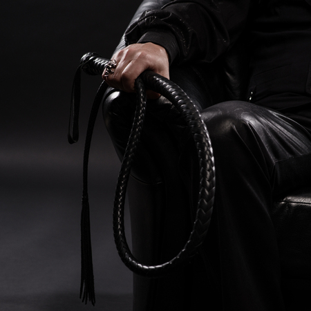 male hand holding black leather whip Foto de archivo