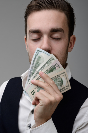 the sweet smell of money. a young man sniffing the money and dreams Stock Photo