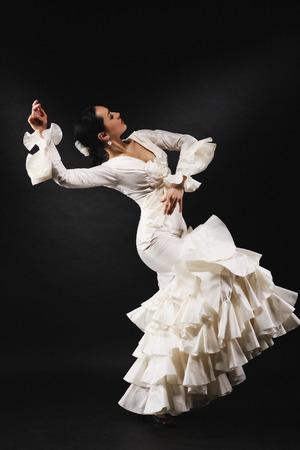 黒い背景に情熱を持ってサルサダンスを実行する若い女性