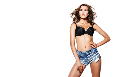beautiful brunette with a sports figure in denim shorts and a black bodice posing on white isolated background