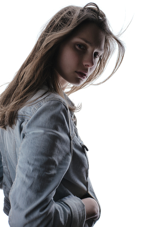 Beautiful mysterious girl with full lips and long hair in a denim jacket.