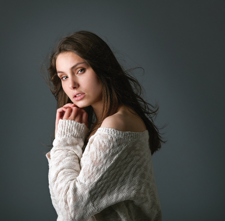Fashion shot of a gorgeous girl with an elegant up-do wearing a warm winter sweater. Foto de archivo