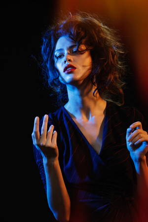 beautiful brunette in the glow of blue and red light. Theatre - a game actor and light