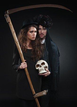 Classic vintage woman poses with black roses and her husband in makeup for All Souls Day