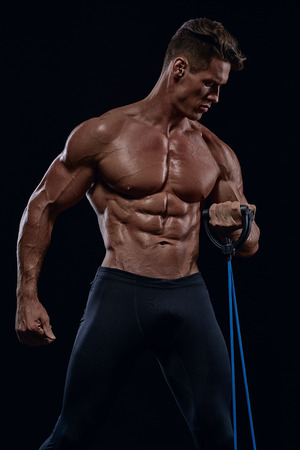 young charismatic bodybuilder exercise on muscles drying using an expander