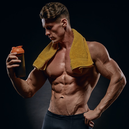 young handsome bodybuilder drinking water after workout