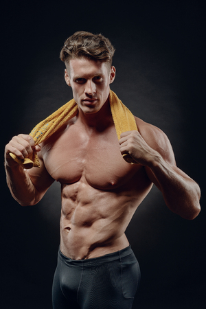 young handsome man after fitness workout with a yellow towel around his neck