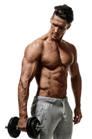 joven culturista guapo sin camisa pantalones deportivos con una mancuerna en la mano y muestra los músculos en los brazos, el pecho y la prensa. Aislado en el fondo blanco.
