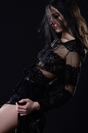 beautiful young brunette in a lace dress on a black background Foto de archivo