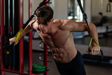muscular bodybuilder training on simulator in the gym. Chest training in gym Stock Photo