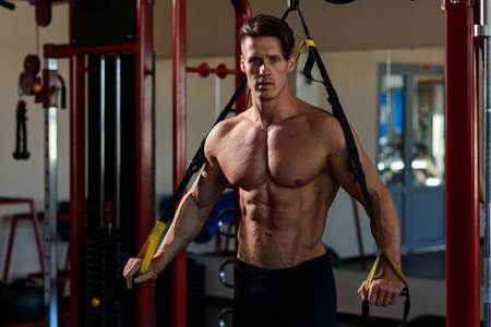 muscular bodybuilder training on simulator in the gym