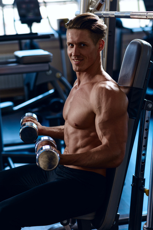 athletic guy workout with dumbbells, perfect shoulders, biceps, triceps and chest. Handsome power athletic man in training pumping up muscles with dumbbells in a gym.