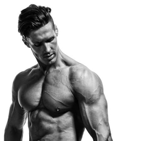 young handsome bodybuilder shows muscles on the arms, chest and press. Studio shot over white. Black and white.