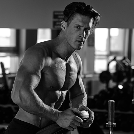 young handsome muscular bodybuilder preparing to exercise in the gym. Foto de archivo