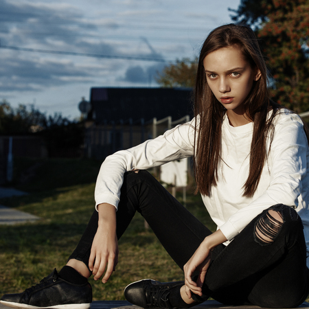beautiful young brown-haired woman sitting on the street Foto de archivo