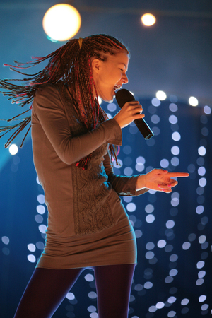 young beautiful girl with a microphone in hand, singing on stage in the rays of light Foto de archivo