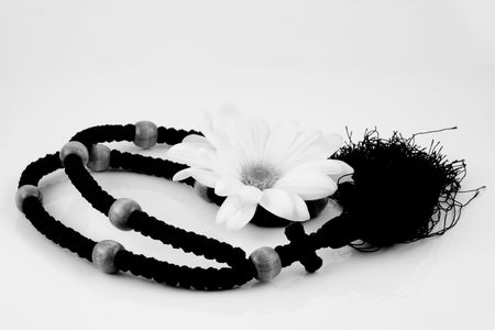 Black & white photo of rosary with white flower