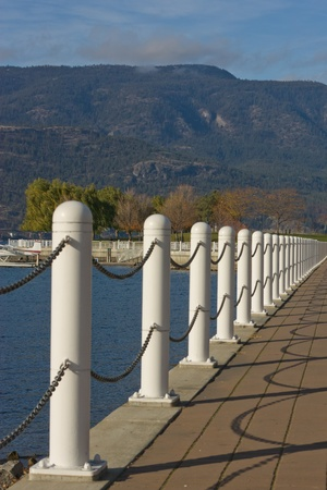 white chain handrails along lakeshore with mountain view