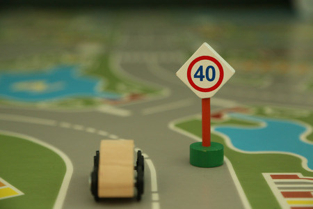 city limit: mini wooden road sign speed limit 40 and mini wooden car - imitation of a typical situation on the street. Stock Photo