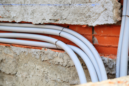 water pipes: Plastic water pipes in the wall outside Stock Photo