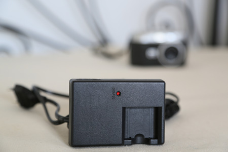 Battery charger for digital camera is placed close to the digital camera itself photo