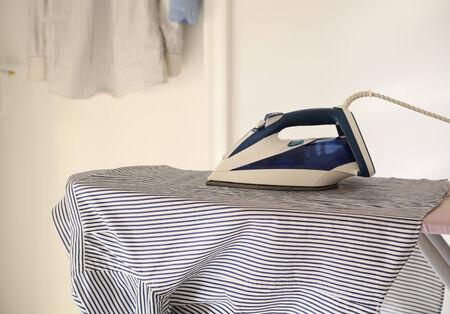 Het shirt en het strijkijzer op de strijkplank Opknoping shirt in de achtergrond