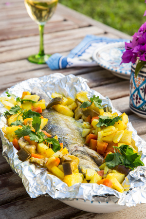 Baked sea bass with vegetables in the aluminum foil