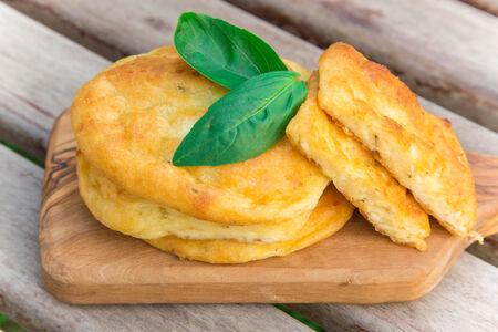 オリーブの木製まな板の上塩味のカッテージ チーズのパンケーキ