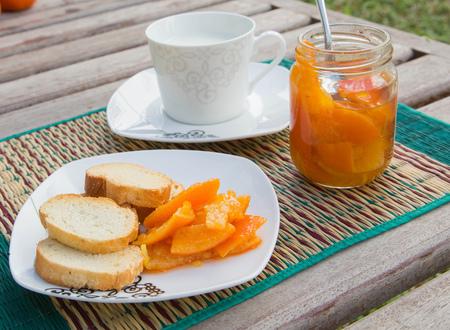 dessert plate: Marmellata di mandarino fatta in casa e alcune fette di pane fresco sul piccolo piatto da dessert quadrato. Vetro aperto di mandarino marmellata e una tazza di latte in background Archivio Fotografico